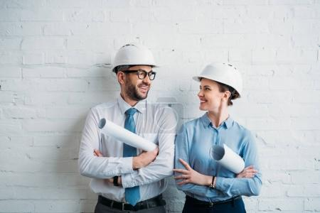 architects in hard hats standing in front of white brick wall with blueprints