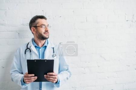 male doctor with clipboard in front of white brick wall