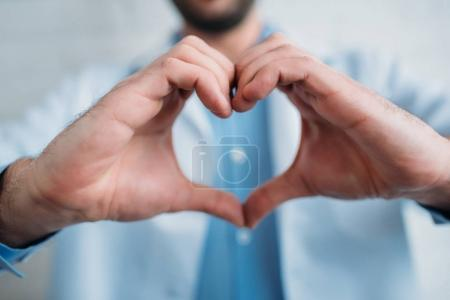 cropped shot of doctor showing heart sign with hands