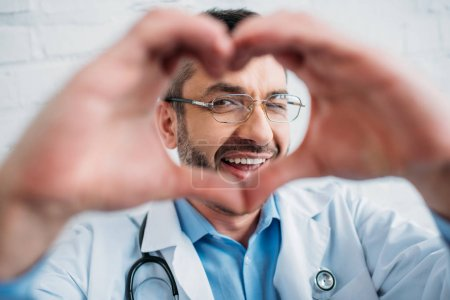 happy handsome doctor showing heart sign with hands