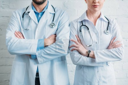 cropped shot of doctors with crossed arms standing in front of white brick wall