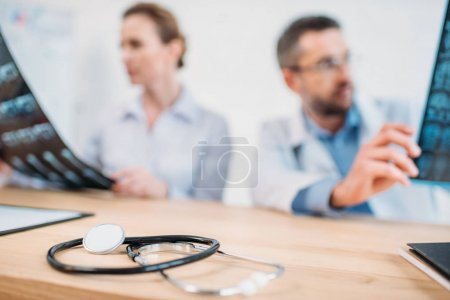 close-up shot of stethoscope on desk with doctors examining x-ray scans blurred on background