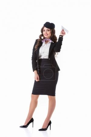 attractive stewardess throwing paper plane isolated on white