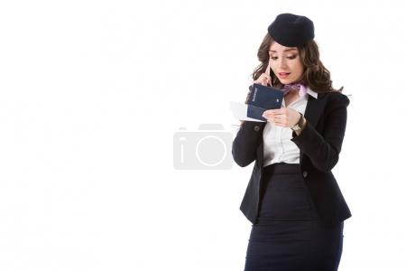 attractive stewardess talking by smartphone and looking at tickets and passport isolated on white