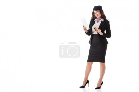 beautiful stewardess standing with tablet and credit card isolated on white