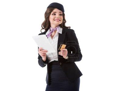 Photo pour Sourire d'hôtesse de l'air attrayant tenant la tablette et carte de crédit isolé sur blanc - image libre de droit