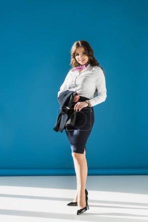 Photo pour Attrayant hôtesse de l'air regardant caméra sur bleu - image libre de droit