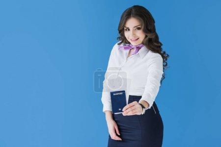 attractive stewardess showing passport with tickets isolated on blue