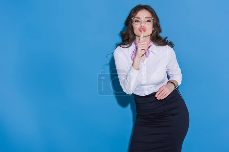attractive stewardess showing silence gesture on blue