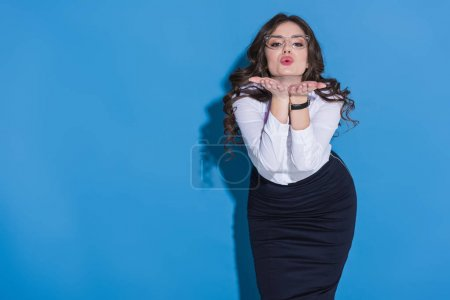 Photo for Attractive stewardess sending air kiss on blue - Royalty Free Image