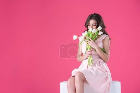 Photo pour Attrayant fille renifler bouquet de tulipes isolées sur rose - image libre de droit