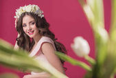 beautiful girl with flowers wreath on head isolated on burgundy
