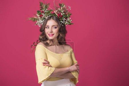schönes Mädchen mit Blumenkranz auf dem Kopf, stehend mit verschränkten Armen isoliert auf Burgunder