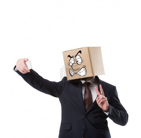 businessman with cardboard box on head taking selfie on smartphone isolated on white
