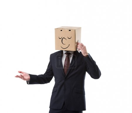 relaxed businessman with cardboard box on head talking on smartphone isolated on white