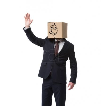 businessman with cardboard box on head and happy face on it waving hand isolated on white