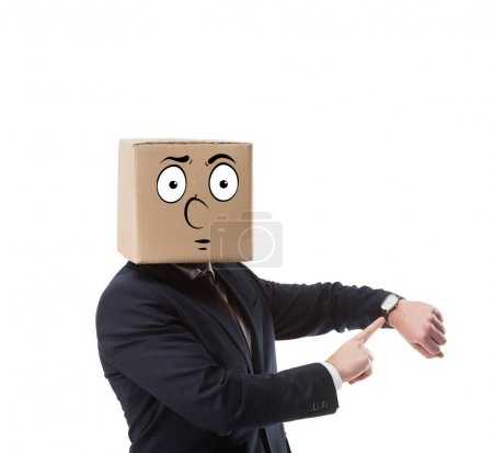 businessman with cardboard box on head pointing on wristwatch isolated on white