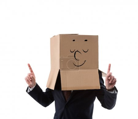 relaxed businessman with cardboard box on head pointing up with fingers  isolated on white
