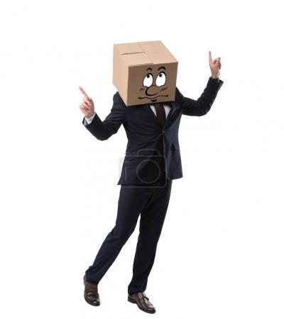 happy businessman with cardboard box on head pointing up, isolated on white