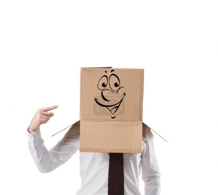 cheerful businessman pointing on cardboard box on his head isolated on white