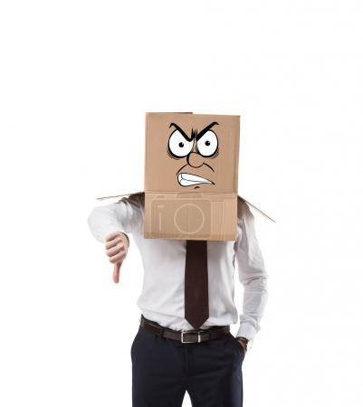 angry businessman with cardboard box on his head showing thumb down isolated on white