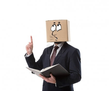 businessman with cardboard box on head holding folder and pointing up with finger isolated on white