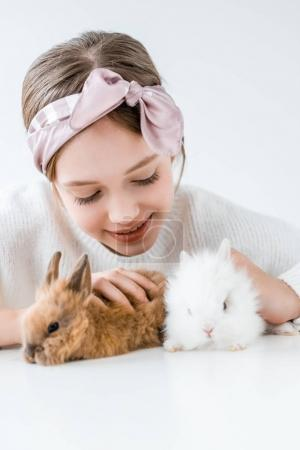 happy child playing with adorable furry rabbits on white