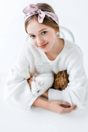 cute happy girl holding furry rabbits and smiling at camera on white