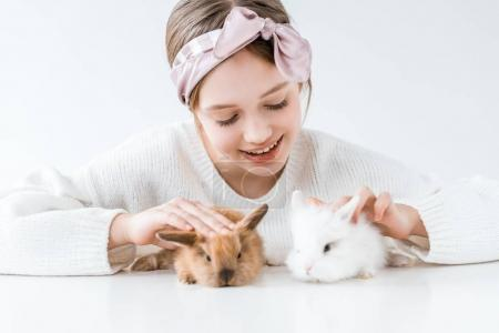 Photo for Beautiful happy girl playing with adorable furry rabbits on white - Royalty Free Image