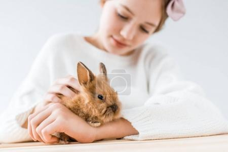 close-up view of smiling girl holding adorable furry rabbit on white