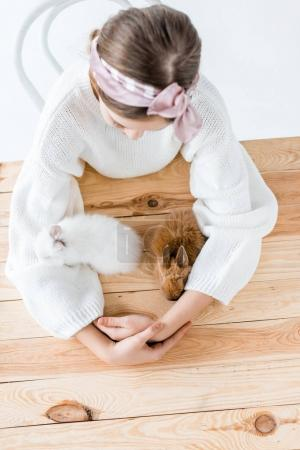 top view of girl sitting at wooden table and looking at cute furry rabbits