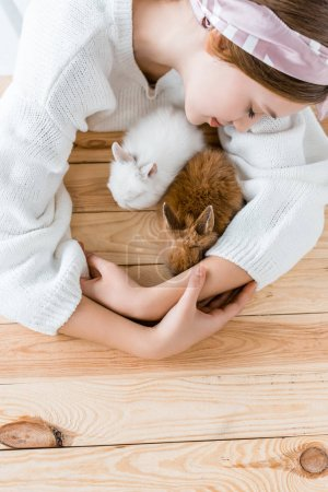 top view of girl hugging cute furry rabbits at wooden table