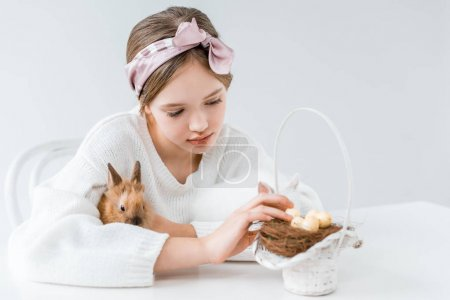 cute little girl hugging rabbit and looking at basket with easter eggs in nest