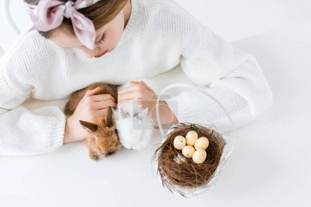 cropped shot of girl looking at cute furry rabbits and basket with easter eggs in nest