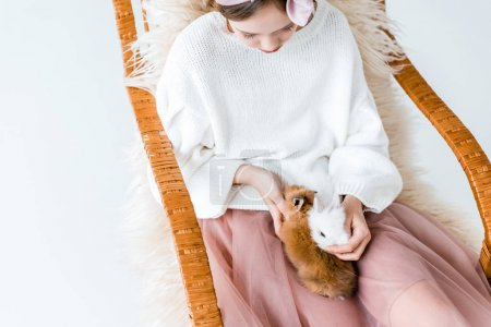 high angle view of girl with cute furry bunnies sitting in rocking chair