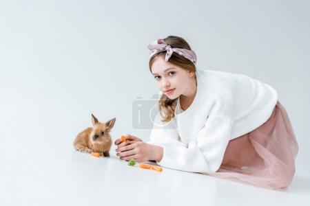 adorable girl looking at camera while feeding rabbit isolated on white