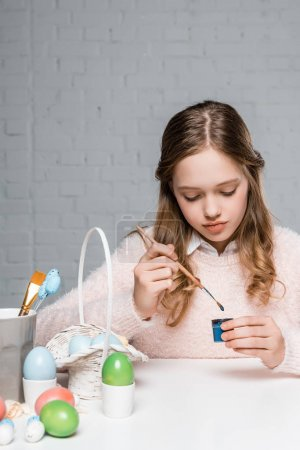 adorable little girl painting easter eggs at table