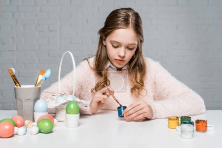 Photo for Beautiful little girl painting easter eggs at table - Royalty Free Image