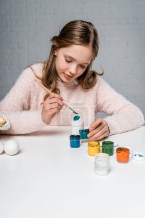 cute smiling girl painting easter eggs at table