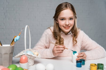 dorable happy girl painting easter egg and smiling at camera