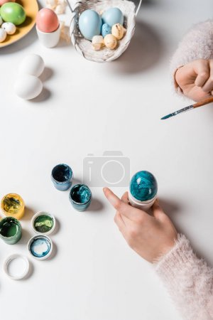 close-up partial view of child painting easter egg at table