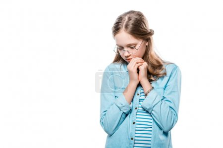 scared teenage girl in eyeglasses looking down isolated on white