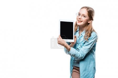 cute teenage girl in eyeglasses holding digital tablet with blank screen and smiling at camera isolated on white
