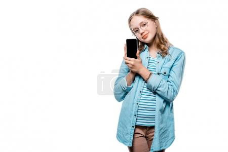 cute ttenage girl in eyeglasses holding smartphone with blank screen and looking at camera isolated on white
