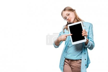 smiling teenage girl holding digital tablet and pointing with finger at blank screen isolated on white