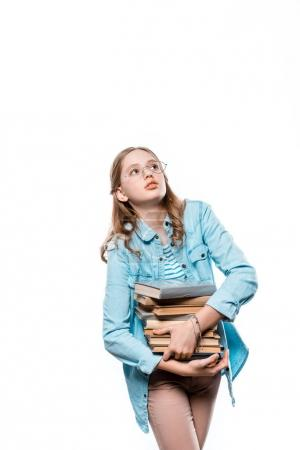 cute teenage girl in eyeglasses holding stack of books and looking up isolated on white