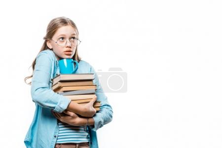 Photo for Girl in eyeglasses holding stack of books with cup on top and looking away isolated on white - Royalty Free Image