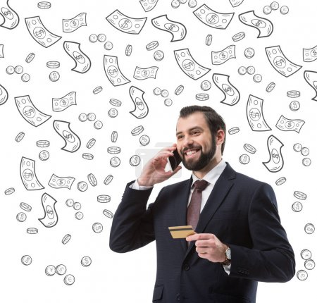 businessman with credit card talking on smartphone, dollar banknotes and coins symbols isolated on white