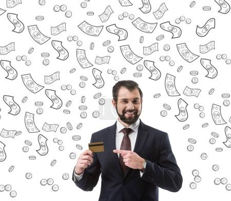 smiling businessman pointing at credit card, dollar banknotes and coins symbols isolated on white