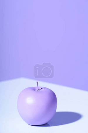 purple apple on violet background with copy space